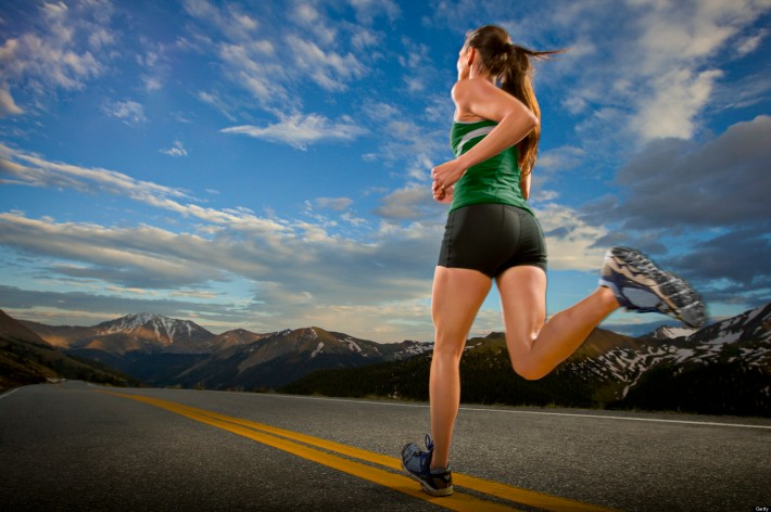 A female road runner runs down a road at dusk at Independence Pass.
